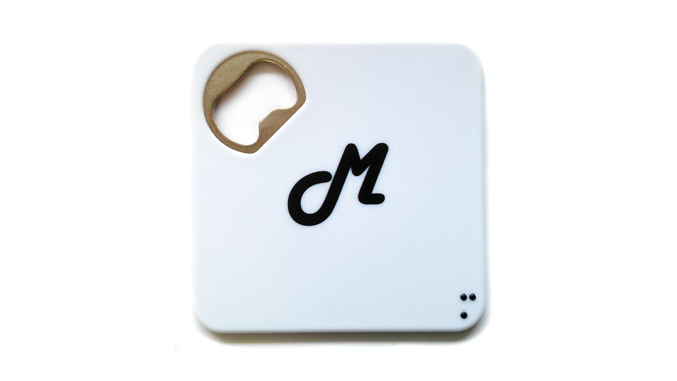 Otvarač boca i podmetač sa slovom M na latinici i Brailleovom pismu